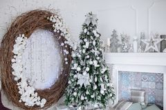 Christmas and New Year decorated white interior room with presents and New year tree and fireplace stock images