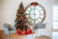 Christmas and New Year decorated white interior room with presents and New year tree with red decor ball. Grey sofa and royalty free stock photos