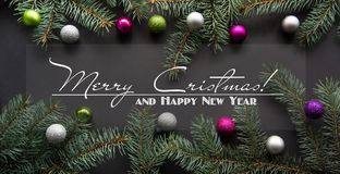 Christmas or New Year decoration background: fir-tree branches, colorful glass balls on black Stock Photos