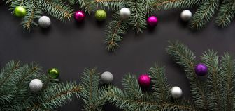 Christmas or New Year decoration background: fir-tree branches, colorful glass balls on black Royalty Free Stock Photos