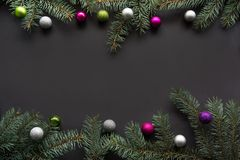 Christmas or New Year decoration background: fir-tree branches, colorful glass balls on black background with copy space. Top view Royalty Free Stock Image