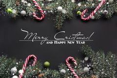 Christmas or New Year decoration background: fir-tree branches, colorful glass balls on black. Stock Photo