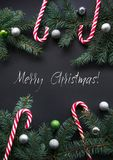 Christmas or New Year decoration background. Fir tree branches, candy, colorful balls on black background with copy space. Royalty Free Stock Photo