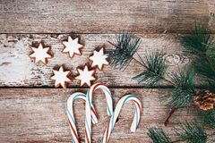 Christmas or New Year decoration background: fur tree branches, candy on wood background. Christmas or New Year decoration background: fur-tree branches, silver Royalty Free Stock Images
