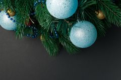 Christmas or New Year decoration background: fur-tree branches, colorful glass balls on black grunge background. Christmas composi. Tion. Flat lay. Top view royalty free stock photos