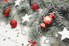 Christmas or New Year decoration background: fur-tree branches, colorful glass balls and glittering stars on white Royalty Free Stock Images