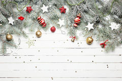 Christmas or New Year decoration background: fur-tree branches, colorful glass balls and glittering stars on white Royalty Free Stock Photo