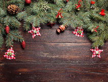 Christmas or New Year decoration background: fur-tree branches, colorful glass balls and glittering stars on wooden Royalty Free Stock Photo