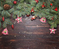 Christmas or New Year decoration background: fur-tree branches, colorful glass balls and glittering stars on wooden Stock Photos
