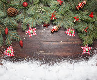 Christmas or New Year decoration background: fur-tree branches, colorful glass balls and glittering stars on wooden Royalty Free Stock Image