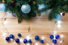Christmas or New Year decoration background: fur-tree branches, colorful glass balls on wooden background. Christmas composition. Flat lay. Top view. Copy stock photos