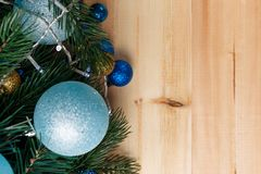 Christmas or New Year decoration background: fur-tree branches, colorful glass balls on wooden background. Christmas composition. Flat lay. Top view. Copy royalty free stock image