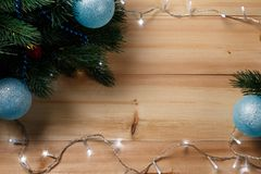 Christmas or New Year decoration background: fur-tree branches, colorful glass balls on wooden background. Christmas composition. Flat lay. Top view. Copy stock photo
