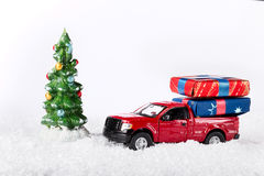 Christmas or New Year decoration background: toy red truck car w. Ith presents near the xmas tree on snow white royalty free stock image