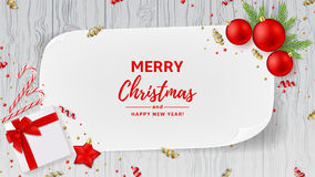 Christmas or New Year decoration banner. Top view on Xmas composition with gift box, golden confetti and balls. Festive backdrop with greeting card and on wooden Royalty Free Stock Photo