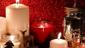 Christmas and New Year Decoration. Blurred Bokeh Holiday Background. Red candles flicker alongside. Mason Jar, Candy canes. Christmas and New Year Decoration stock footage