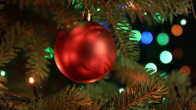 Christmas and new year decoration. Christmas tree decorations red ball with blurred fairy lights garland stock video