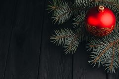 Christmas New Year decoration composition. Top view of fur-tree branches and balls frame on wooden background with place for your royalty free stock image