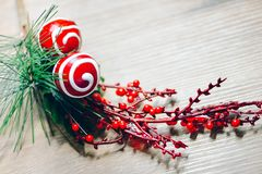 Christmas and New year decoration. Green fir tree branch with red berries. Red lollypops, white chocolate glaze. Traditional sweets on wooden table. Photo for royalty free stock images