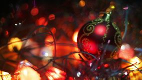 Christmas and New Year Decoration. Hanging Bauble close up. Abstract Blurred Bokeh Holiday Background. A red toy ball stock footage