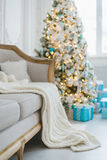 Christmas or new year decoration at Living room interior and holiday home decor concept. Calm image of blanket on a vintage sofa w. Ith tree and gifts. Selective Royalty Free Stock Image