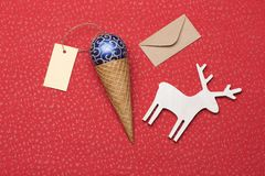 Christmas or New Year decoration on red textured background. Christmas or New Year decoration with blue silver christmas ball, ice cream cone, yellow tag with Royalty Free Stock Photography
