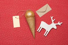 Christmas or New Year decoration on red textured background. Christmas or New Year decoration with rose gold christmas ball, ice cream cone, yellow tag with Royalty Free Stock Image