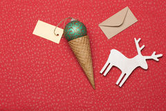 Christmas or New Year decoration on red textured background. Christmas or New Year decoration with green gold christmas ball, ice cream cone, yellow tag with Royalty Free Stock Photography
