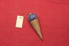 Christmas or New Year decoration on red textured background. Christmas or New Year decoration with purple silver christmas ball, ice cream cone and yellow tag Royalty Free Stock Image