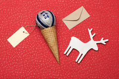 Christmas or New Year decoration on red textured background. Christmas or New Year decoration with silver blue christmas ball, ice cream cone, yellow tag with Royalty Free Stock Photography