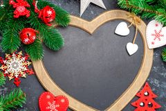 Christmas or New Year decorations background: a frame in the shape of a heart is surrounded by branches of a New Year tree Christm stock images