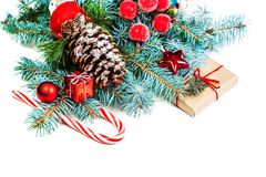 Christmas or New Year decorations background with pine cones, fir branches, gift boxes, red berries and candy isolated on white b royalty free stock photography