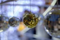 Silver christmas disco ball on a blurred festive background in time for new year holiday. Christmas and new year decorations. Christmas ball hanging on a pine royalty free stock images