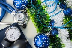 Christmas New Year decorations and medical diagnostic devices. Stethoscope with a device for measuring pressure or sphygmomanomete. R lie near the artificial stock photo