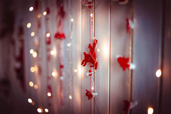 Christmas and new year decorations with red toy deers and yellow lights hanging on a wooden texture wall. New Year and Christmas holidays festive decorations Stock Photo