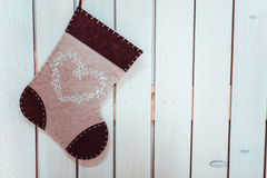 Christmas and New Year decorative sock. Beautiful wool decorative sock with a heart shape on it hanging on a wooden wall Royalty Free Stock Photo