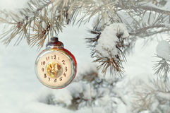 Christmas, New Year eve background -New Year Christmas glass toy clock showing the New Year Eve, on snowy fir tree Royalty Free Stock Photography