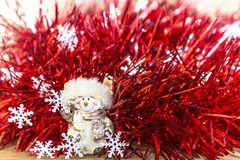 Christmas and New Year festive background of red tinsel, snowflakes and smiling snowman. royalty free stock photography