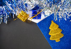 Christmas or New Year flat composition. Fir tree toy and gift. Black paper with blank page. Stock Photos