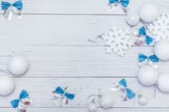 Christmas or new year flat lay composition in silver white and blue colors with balls snowflake and bows on white wood.  stock images