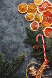 Christmas or New Year flat lay home decor, dry oranges, cinnamon, candies and fir branches on concrete background. Cozy winter hom. Christmas or New Year flat stock images