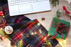 Christmas, New Year flat lay with a laptop keyboard, Scottish tartan and lights on the wooden background. stock photo