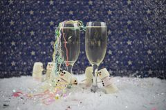 Christmas or New Year food and drink photography image using marshmallows shaped as snowman in snow with glasses of champagne stock photo