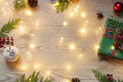 Christmas, New Year frame with festive lights on the wooden background. Winter holiday celebration top view card. stock photography