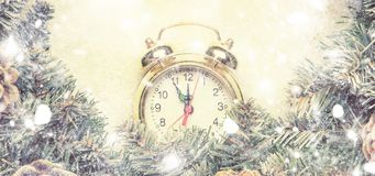 Christmas or New Year frame flat composition, banner, with alarm. Clock and green snow fir branches, pine cones, white gray background, top view royalty free stock photos