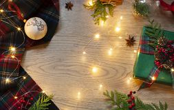 Christmas, New Year frame with Scottish tartan pattern and festive lights on the wooden background. royalty free stock photos