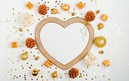 Christmas or new year frame in the shape of a heart composition. christmas decorations in gold colors on white background with emp. Christmas or new year frame stock image