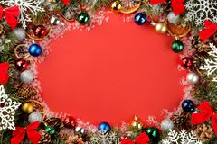 Christmas and New Year frame for text with a Christmas tree and colored Christmas decorations on a red bright background. view fro. M above stock photography