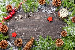 Christmas or new year frame for your project with copy space. Christmas fir trees in snow with cones, vintage clock, decorative st. Ars, red ribbon and 2018 stock photography