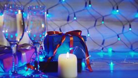 Christmas and new year gift boxes, candles and two glasses of champagne. Close up shot of christmas and new year gift boxes, candles and two glasses of champagne stock footage